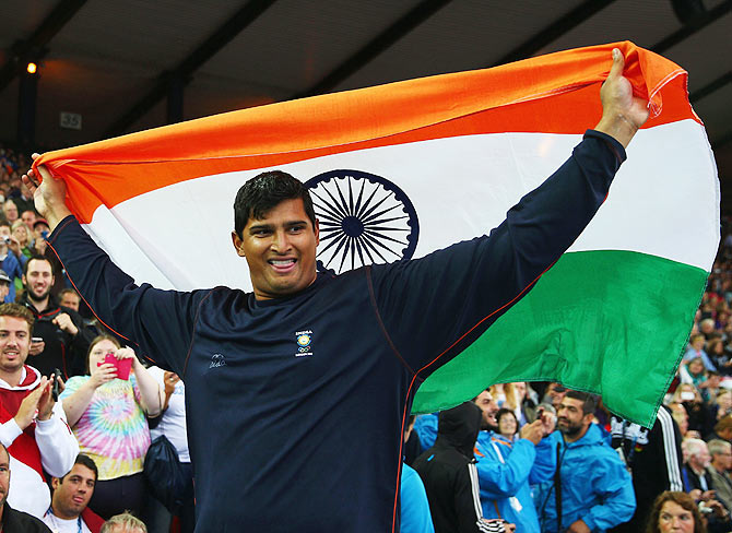 Vikas Shive Gowda of India celebrates winning gold in the men's discus throw final