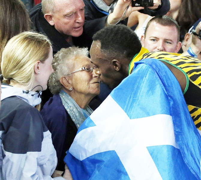 Jamaica's Usain Bolt kisses a woman in the stands after Jamaica won the men's 4x100m relay final at the 2014 Commonwealth Games in Glasgow
