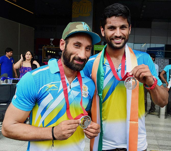 Indian Hockey team captain Sardara Singh (left) and the team's top scorer Rupinder Pal Singh pose for photographers on their arrival from the Glasgow Commonwealth on Tuesday