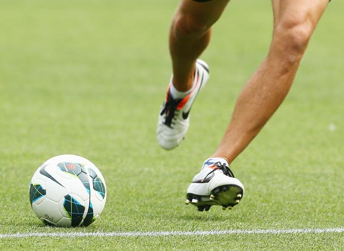 A player kicks a soccer ball