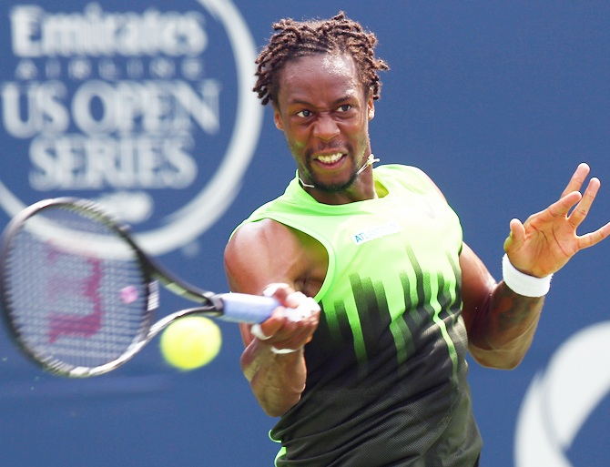 Gael Monfils of France returns a shot to Novak Djokovic of Serbia