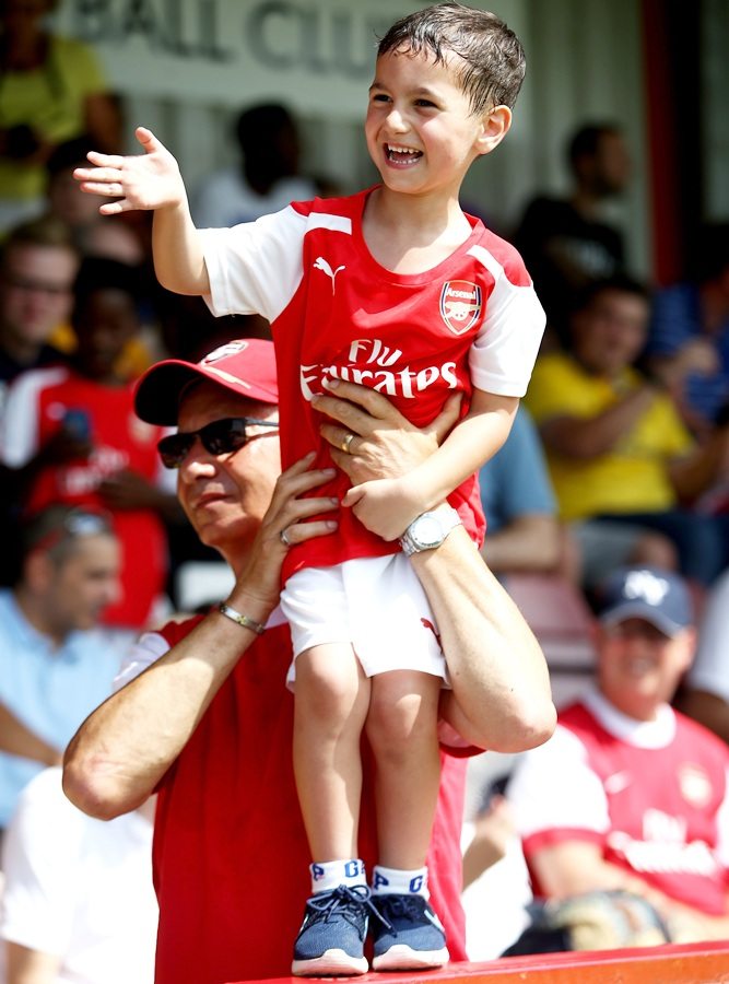 A young Arsenal fan waves as Arsenal manager Arsene Wenger walks onto the pitch