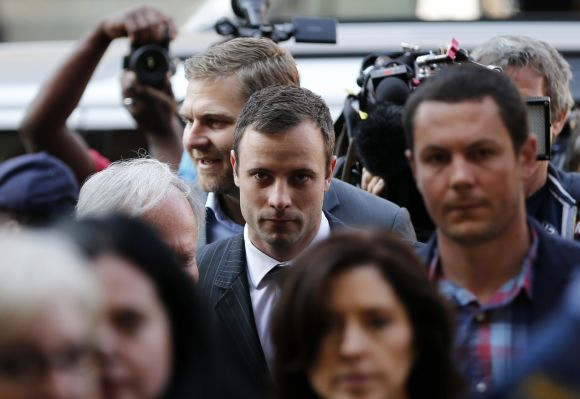 Paralympic track star Oscar Pistorius (C) arrives for the closing arguments in his murder trial, at the high court in Pretoria
