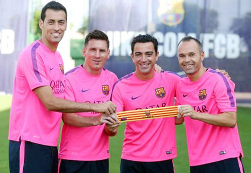 Barcelona's Sergio Busquets, Lionel Messi, Xavi Hernandez and Andres Iniesta pose with the captain's armband on Thursday