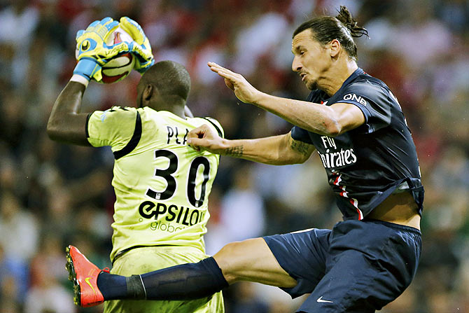 Johny Placide (left), goalkeeper of Stade Reims fights for the ball with Zlatan Ibrahimovic of Paris St Germain during their French Ligue 1 soccer match at the Gustave Delaune Stadium in Reims on Friday
