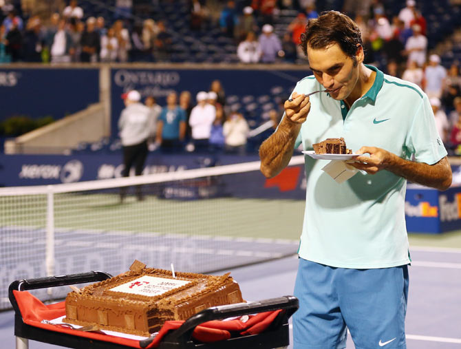 Roger Federer of Switzerland has a piece of his birthday cake after his quarter-finals win against David Ferrer of Spain during the Rogers Cup at Rexall Centre at York University in Toronto on Friday