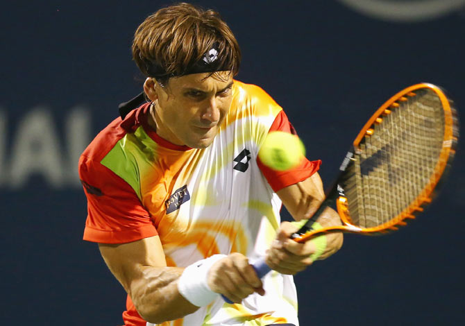 David Ferrer of Spain returns a shot to Roger Federer of Switzerland on Friday
