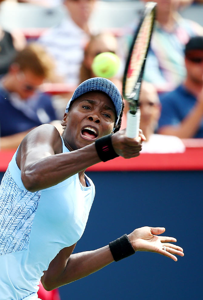 Venus Williams of the USA returns a shot to Carla Suarez Navarro of Spain in their quarter-final match on Friday