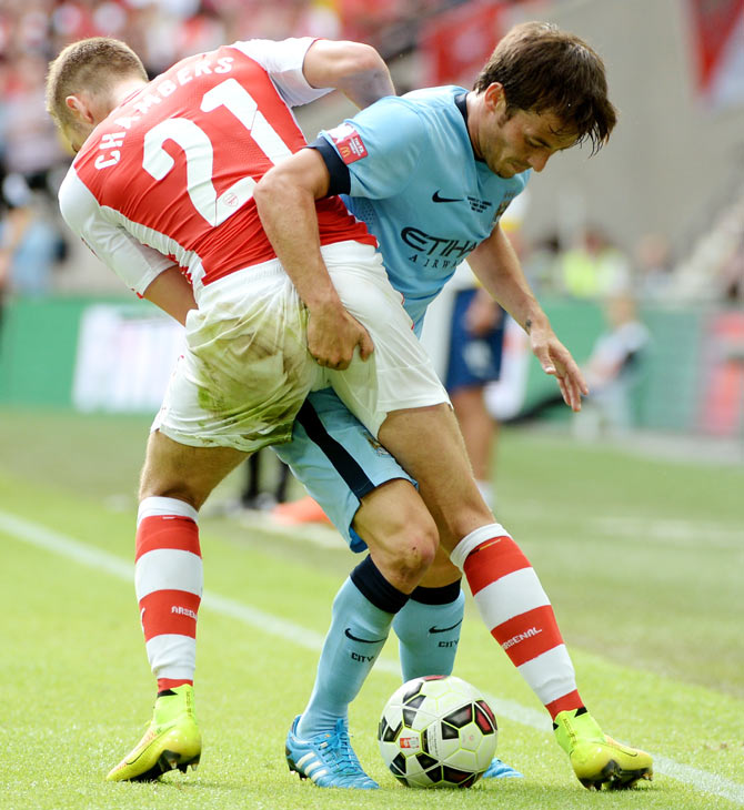 Calum Chambers of Arsenal grapples with David Silva of Manchester City as they fight for possession during their FA Community Shield match at Wembley Stadium in London on Sunday
