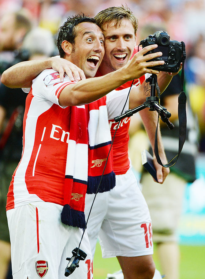 Santi Cazorla of Arsenal and team-mate Nacho Monreal (right) celebrate by clicking a selfie after winning the FA Community Shield final against Manchester City on Sunday