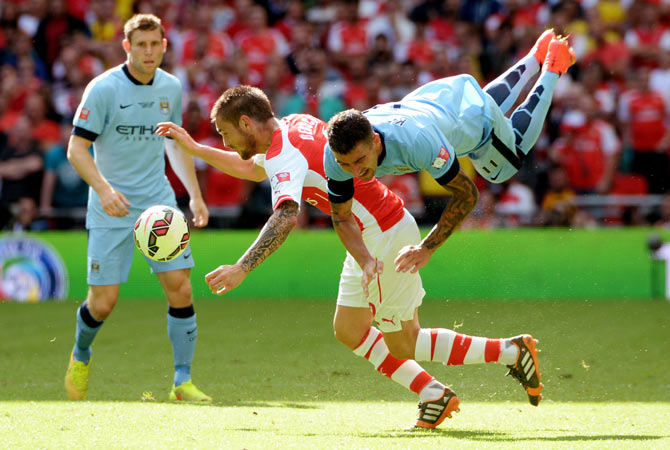 Aleksandar Kolarov of Manchester City is challenged by Mathieu Debuchy of Arsenal during their FA Community Shield match on Sunday