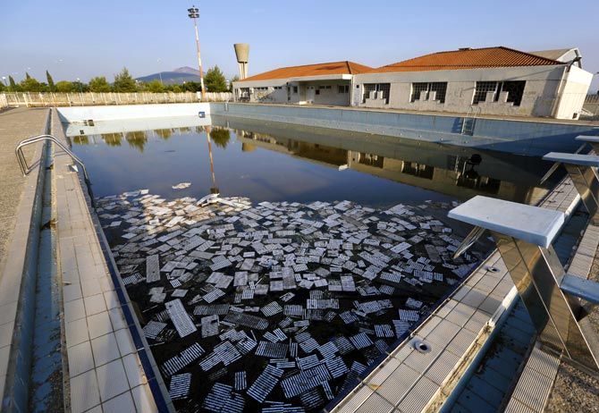 Garbage floats in a deserted swimming pool at the Olympic Village in Thrakomakedones, north of Athens