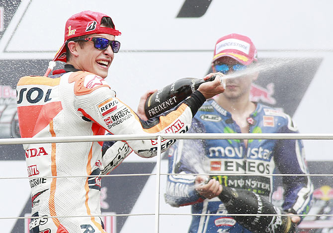 Honda MotoGP rider Marc Marquez (left) of Spain celebrates along with compatriot and Yamaha MotoGP rider Jorge Lorenzo on the podium on Sunday. Lorenzo finished second in the race