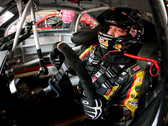 Tony Stewart, driver of the #14 Rush Truck Centers/Mobil 1 Chevrolet, sits in his car in the garage area during practice for the NASCAR Sprint Cup Series Cheez-It 355 at Watkins Glen International on Friday