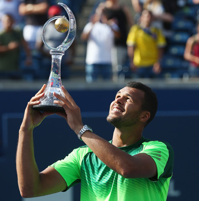 Jo-Wilfried Tsonga of France holds up the Rogers Cup trophy after his win against Roger Federer of Switzerland during the finalRexall Centre at York University in Toronto on Sunday