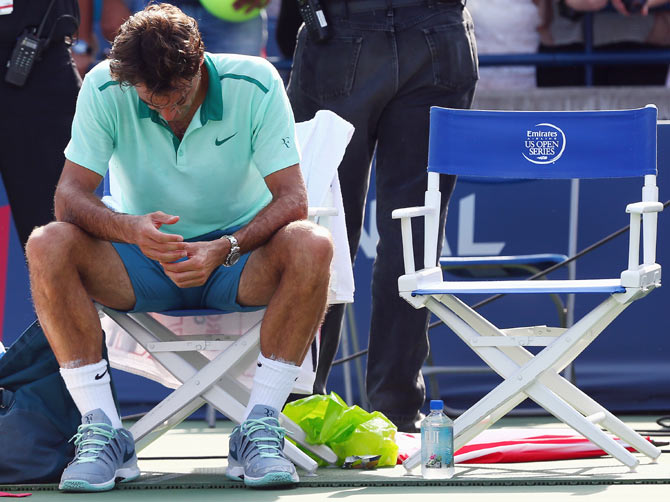 Roger Federer of Switzerland sits in his chair after his loss to Jo-Wilfried Tsonga of France in the final match of the Rogers Cup at Rexall Centre at York University on Sunday