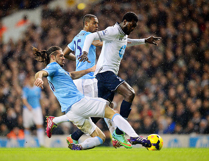 Martin Demichelis of Manchester City tackles Emmanuel Adebayor of Tottenham Hotspur