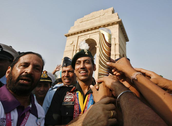 Rajyavardhan Singh Rathore (centre) with the baton during the Commonwealth Games Queen's Baton Relay in New Delhi on October 1, 2010.