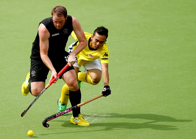 Bradley Shaw of New Zealand is challenged by Meor Hasan of Malaysia (right)