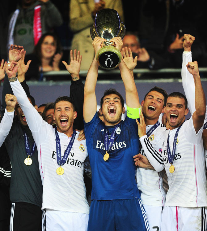 Real Madrid players (left to right) Sergio Ramos, Iker Casillas, Ronaldo and Pepe (right) celebrate with the trophy after the UEFA Super Cup match between Real Madrid and Sevilla FC at Cardiff City Stadium on Tuesday