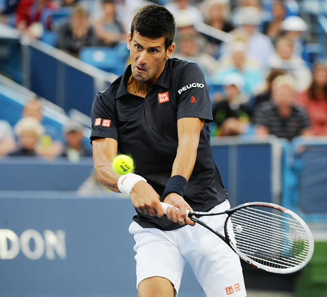Novak Djokovic of Serbia returns to Gilles Simon of France during a match on day 4 of the Western & Southern Open in Cincinnati on Tuesday