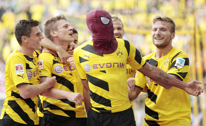Borussia Dortmund's Pierre-Emerick Aubameyang (with Spiderman mask) and teammates celebrate a goal against Bayern Munich during their SuperCup 2014 soccer match in Dortmund on Wednesday