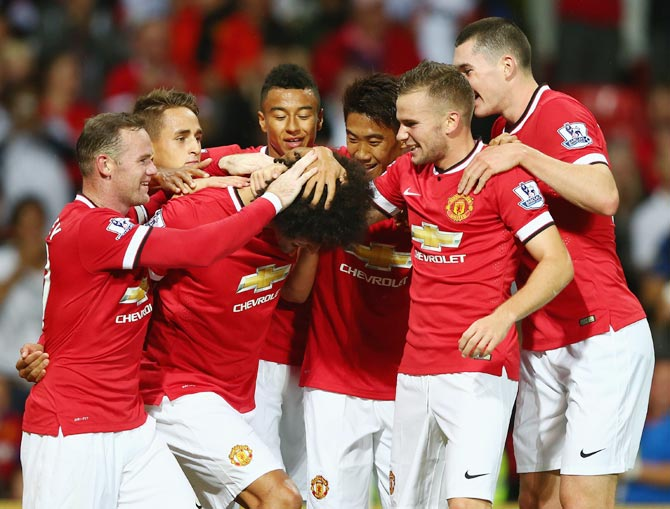 Manchester United players celebrate a goal during the pre-season friendly match against Valencia at Old Trafford in Manchester on August 12, 2014.
