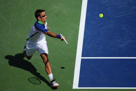 Tommy Robredo of Spain returns to Novak Djokovic of Serbia