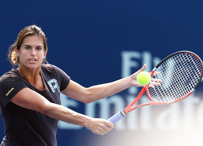 Coach Amelie Mauresmo returns a shot with Andy Murray of Great Britain