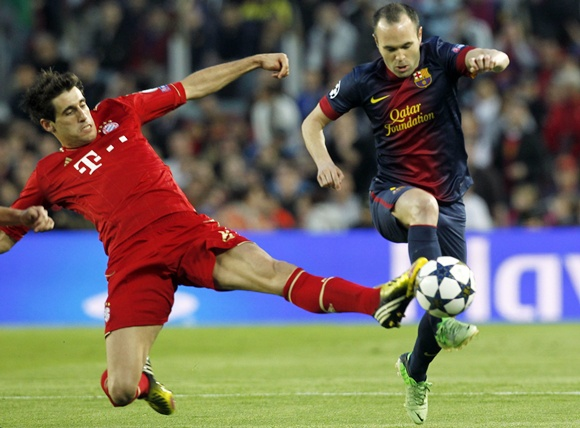 Bayern Munich's Javi Martinez tackles Barcelona's Andres Iniesta