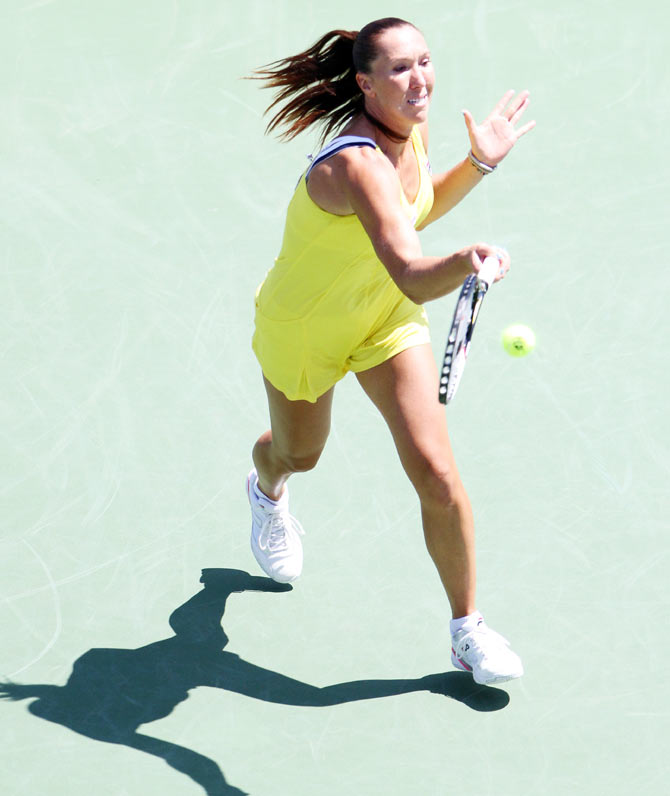 Jelena Jankovic returns a shot against Serena Williams on Friday