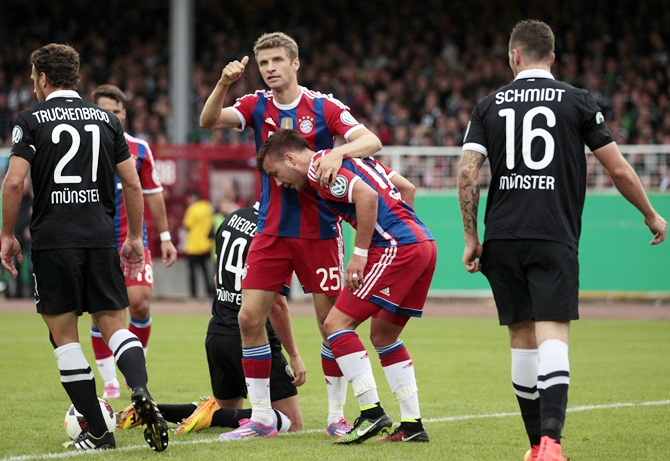 Bayern Munich's Thomas Mueller and teammate Mario Goetze, second right, celebrate a goal against Preussen Muenster
