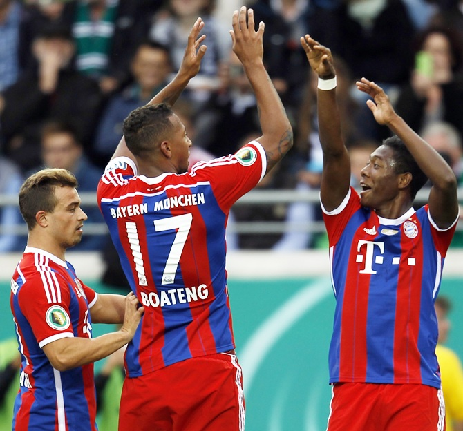 Bayern Munich's Jerome Boateng, centre, and David Alaba, right, celebrate a goal against Preussen Muenster