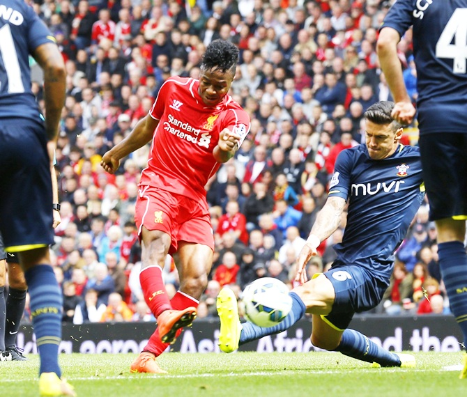 Liverpool's Raheem Sterling,left, is challenged by Southampton's Jose Fonte, right, during their English Premier League soccer match at Anfield