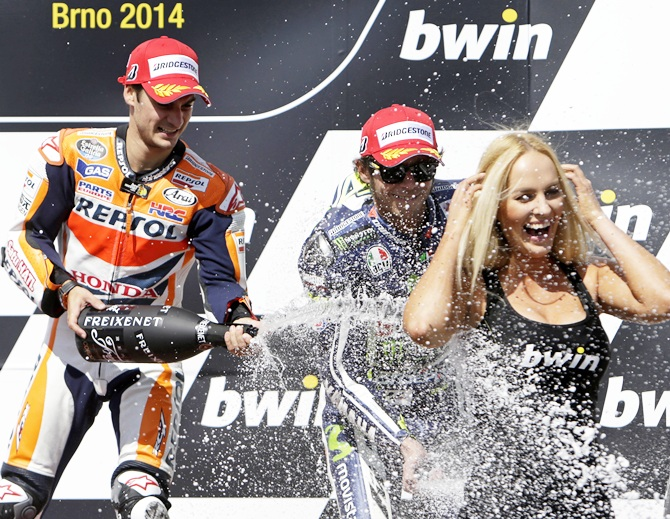 Winner Honda MotoGP rider Dani Pedrosa, left, of Spain and third-placed Yamaha MotoGP rider Valentino Rossi of Italy spray champagne on a hostess after the Czech Grand Prix in Brno