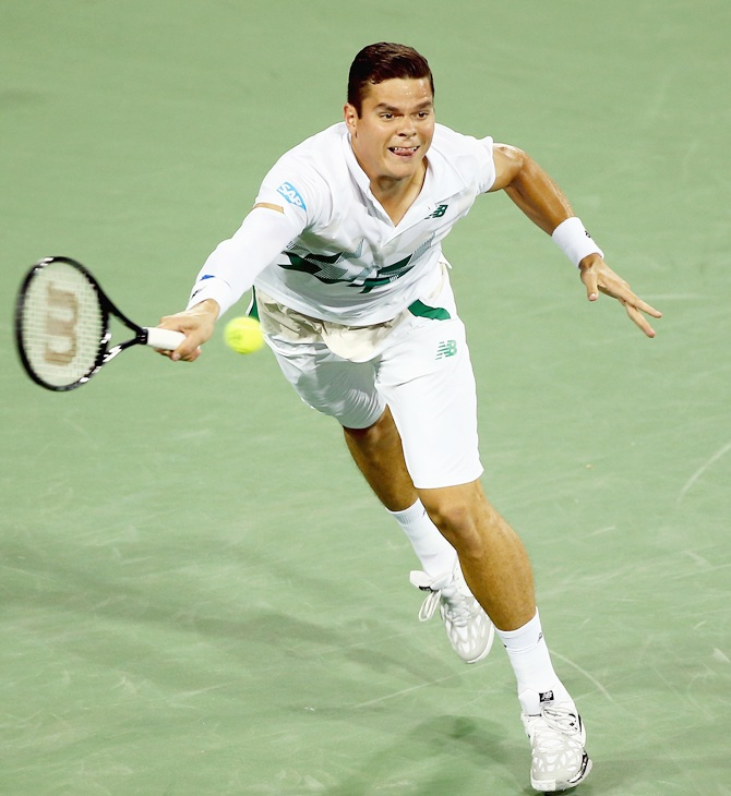 Milos Raonic of Canada hits a return during his match against Roger Federer