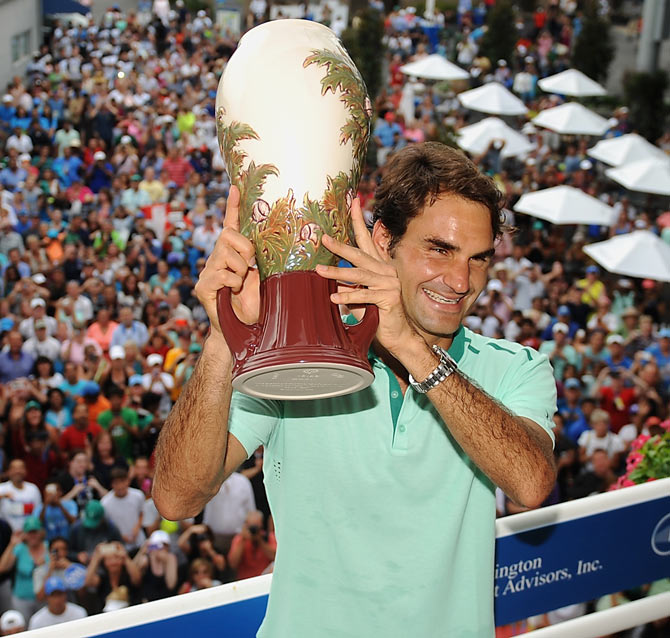 Roger Federer of Switzerland poses with the winner's trophy on the Champion's Balcony after beating David Ferrer of Spain to win the Cincinnati title on Sunday