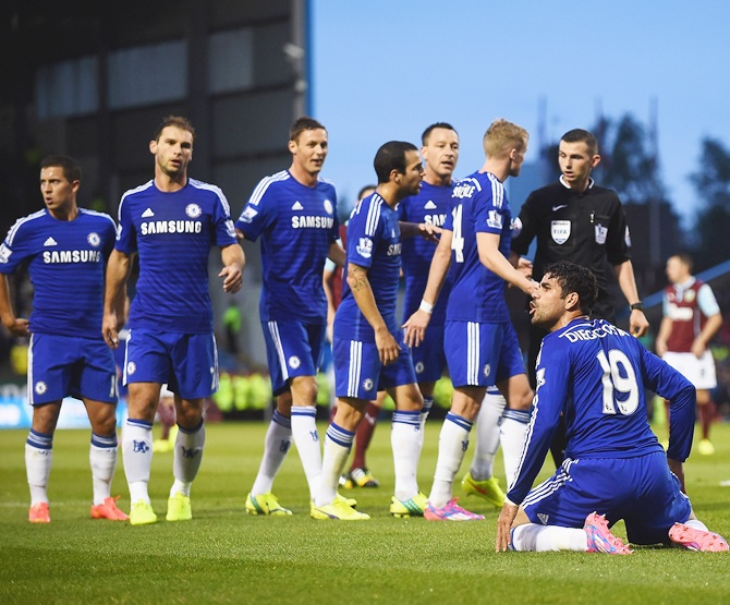 Chelsea players appeal to Referee Michael Oliver, as he books Diego Costa of Chelsea for diving