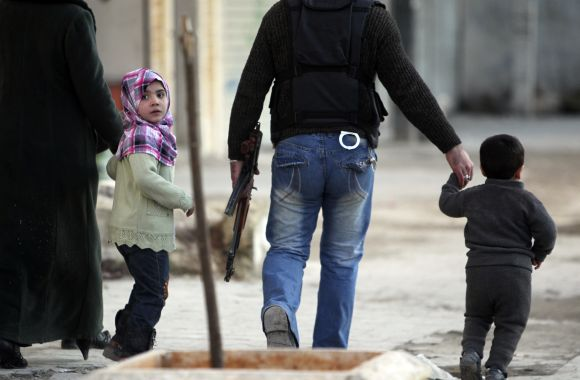 A girl wearing a pink scarf flees with her family from shelling in the al-Masir area in Aleppo