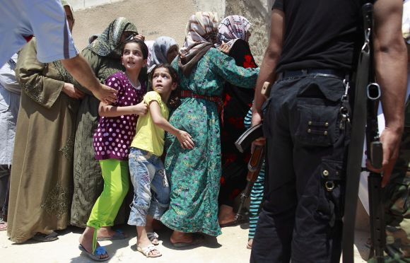 Girls queue to buy bread at the only bakery serving the outskirts of Idlib province