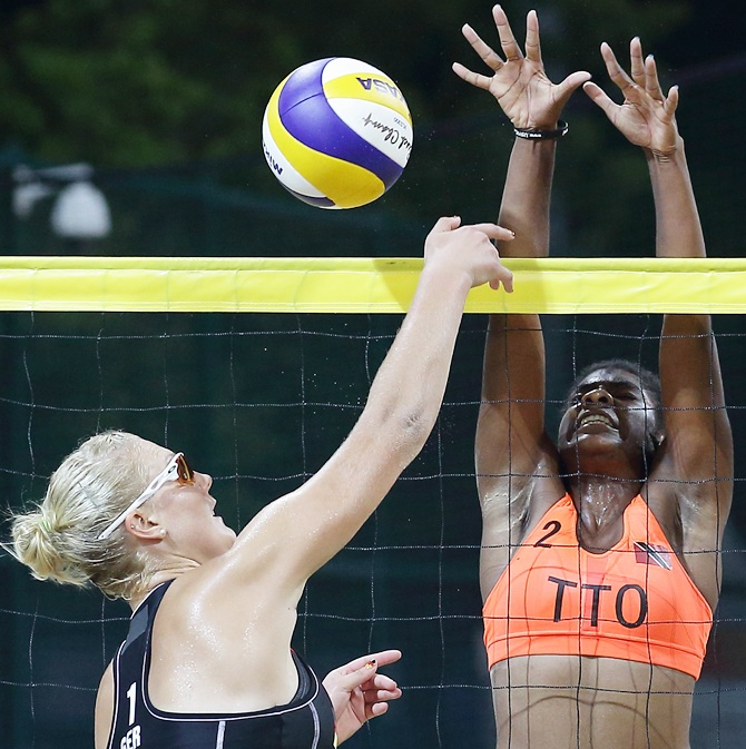 Malika Davidson of Trinidad and Tobago attempts to block Sarah Schneider of Germany shot during the Nanjing 2014 Youth Olympic Beach Volleyball