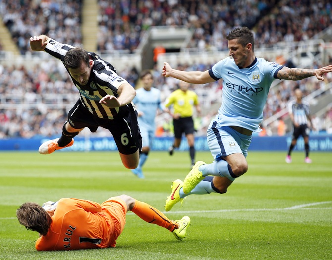 Newcastle United's Mike Williamson, top left, and goalkeeper Tim Krul (bottom) challenge Manchester City's Stevan Jovetic