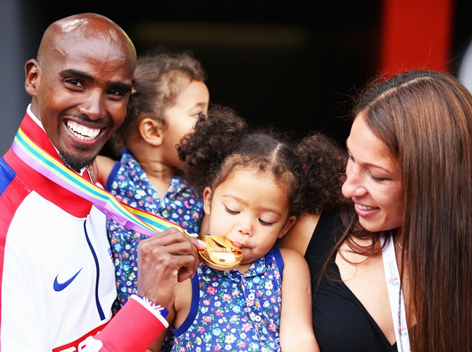 One of Mo Farah's twin daughters bites his gold medal as he poses with his wife Tania and their other twin daughter following his victory in the Men's 5000m Final
