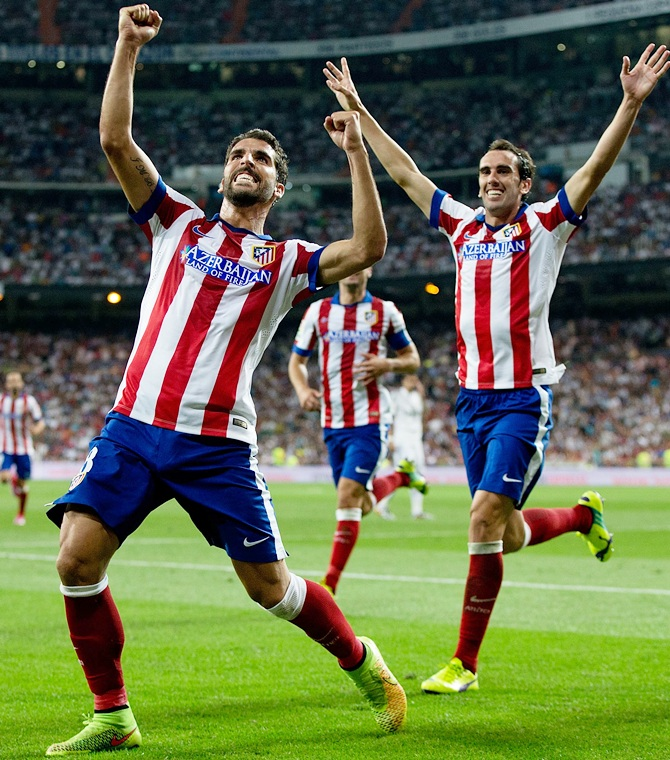 Raul Garcia, left, of Atletico de Madrid celebrates scoring their opening goal with teammate Diego Godin during the Supercopa first leg match between Real Madrid and Club Atletico de Madrid at Estadio Santiago Bernabeu