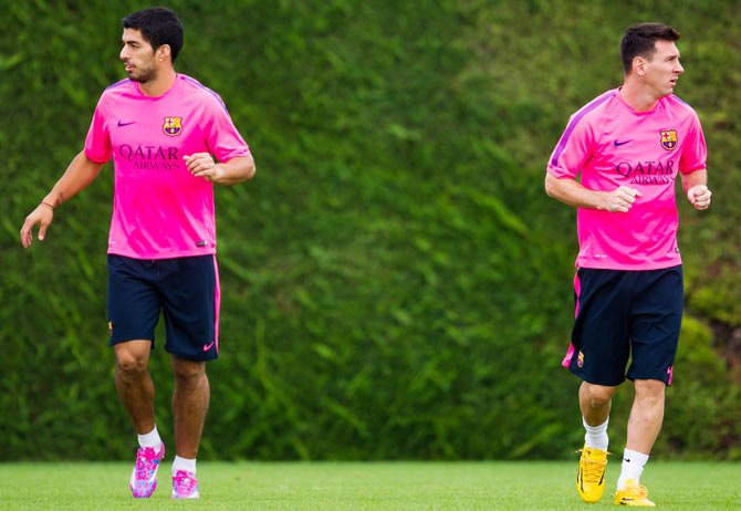 Luis Suarez (left) and Lionel Messi (right) look on during a FC Barcelona training session at Ciutat Esportiva in Barcelona on Sunday