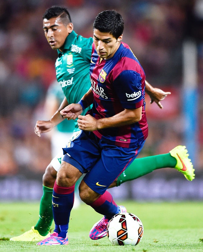 Luis Suarez of FC Barcelona competes for the ball with Luis Delgado of Club Leon