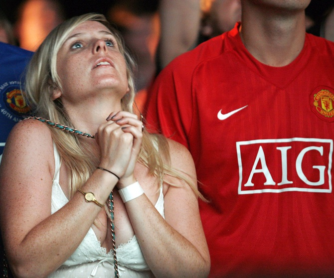 A Manchester United supporter reacts as she watches