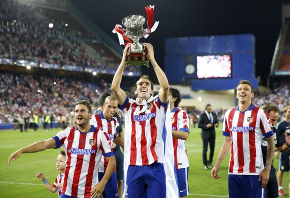 Atletico Madrid's Diego Godin (C), Koke (L) and Mario Mandzukic celebrate with the trophy after they won the Spanish Super Cup against Real Madrid