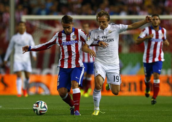 Atletico Madrid's Antoine Griezmann (L) and Real Madrid's Luka Modric fight for the ball during their Spanish Super Cup second leg soccer match
