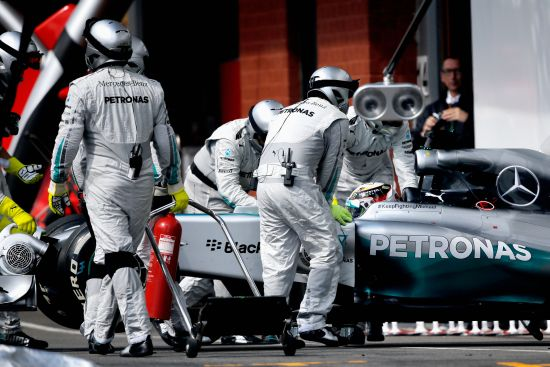 Lewis Hamilton of Great Britain and Mercedes GP is pushed back into the garage after retiring during the Belgian Grand Prix